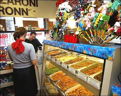 John Reilly, co-owner of Dairy Fresh Candies, works the counter as a customer makes a purchase. 'This is where I come for my sugar fix,' says Susi. The shop, which has been open since 1957, offers a gleaming cornucopia of nuts, dried fruit, chocolate, candy, and Italian olive oils and coffee.