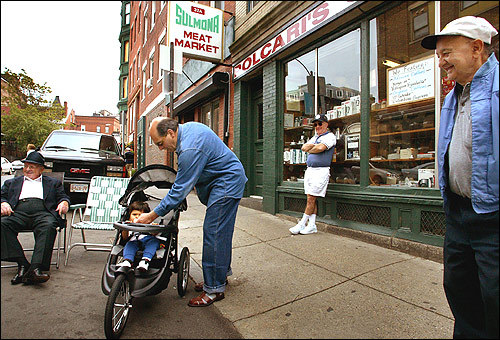 A common scene in the North End finds local residents set up comfortably on street corners, socializing and catching up on the latest news.