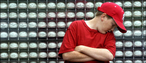 Tim Johnson checks out the wall of baseballs -- each bearing the name of a soldier who died in Iraq -- he helped his father build.