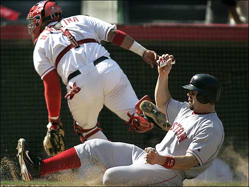 Jason Varitek slides in safely as the ball sails away from Bengie Molina on a fourth inning throwing error by Chone Figgins.