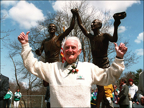 Kelley in front of his statue on Commonwealth Avenue in Newton shortly after it was erected in 1993. The statue depicts a young and an old Kelley, crossing the finish line together.
