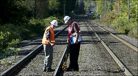 Workmen check the railroad tracks in Beverly near the site where a boy was killed by a train this morning.