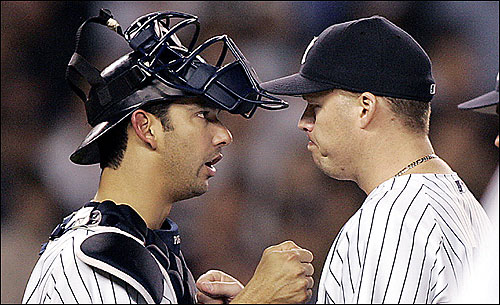 Yankees catcher Jorge Posada (left) gives starting pitcher Jon Lieber a pat for a job well done after he faced his last Red Sox batter.
