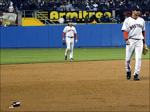As beer bottles (one is seen at bottom left) and other debris rain down on the field, Johnny Damon (left) and Orlando Cabrera (right) head to the middle of the diamond for safety.