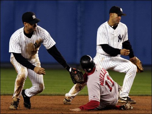 Bill Mueller slides back to second base in the fifth inning on a grounder by Damon that got past the Yankees' Derek Jeter.