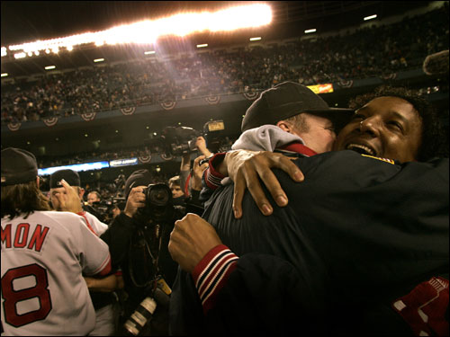Pitchers Curt Schilling and Pedro Martinez embrace on the field as hero hitter Johnny Damon (left) mugs for the cameras.