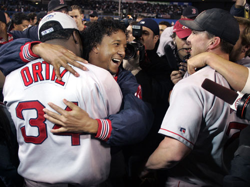 Pedro Martinez hugs David Ortiz, and Trot Nixon and Kevin Millar embrace at right as the Red Sox celebrate on the field at Yankee Stadium.