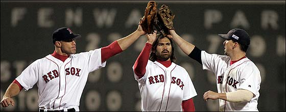 With a victory in Game 2 safely behind them, Red Sox outfielders (left to right) Gabe Kapler, Johnny Damon, and Trot Nixon converge for a celebratory tapping of their gloves.