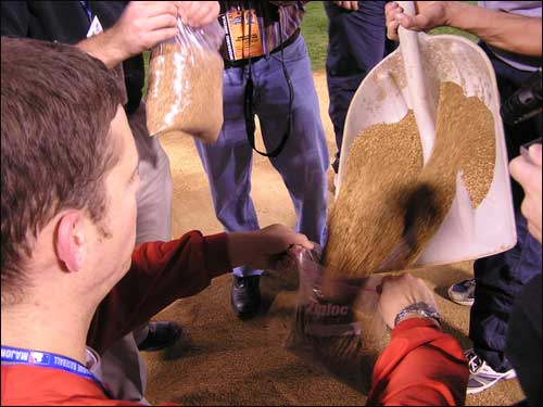Members of the Busch Stadium ground crew bag dirt from the mound for players as mementos and for the Baseball Hall of Fame in Cooperstown.