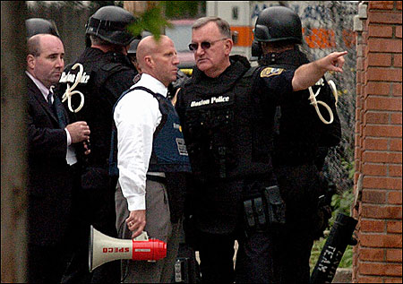 Deputy Superintendent Robert E. O'Toole Jr. (with sunglasses) led an operation in May to apprehend a suspect in a house.