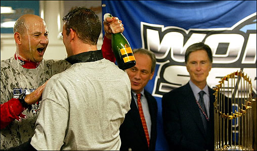 Manager Terry Francona (left) gives general manager Theo Epstein a champagne shower as Larry Lucchino and John W. Henry (right) look on during the postgame festivities.
