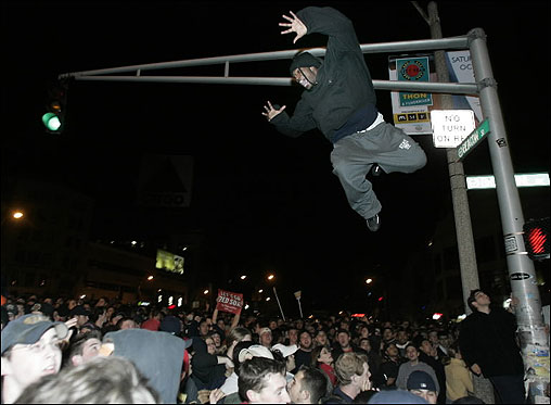 A fan jumps into the crowd from a light pole in Kenmore Square.
