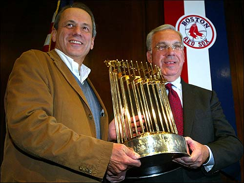 At a City Hall press conference to announce the details of the Red Sox rolling rally, Larry Lucchino (left) held the World Series trophy with Mayor Menino.