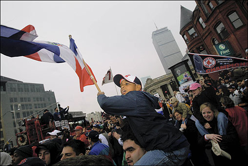 On Boylston Street, Nestor Reyes, 9, waves the Dominican Republic flag atop the shoulders of his dad, Jesus Torres, as the Red Sox victory parade passes by. They are from the city of Bani in the Dominican Republic.
