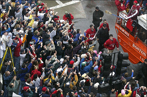 Fans go wild as David Ortiz waves a broom, symbolizing the Sox' sweeping the Cardinals to win the World Series, as he passes by in a duck boat.