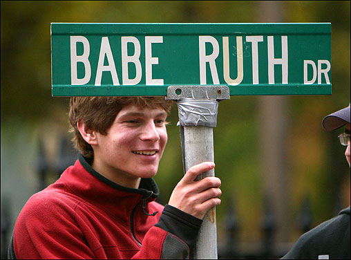 Matt Brockman from Sudbury holds a street sign taken from near Babe Ruth's former residence as he waits for the parade to pass by his location on Tremont Street.