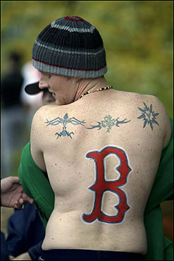 Chris Kiely, 23, of Middleboro, adds a Red Sox 'B' symbol to the tattoos on his back while waiting for the parade to pass. Despite the weather, he vowed to keep his new art exposed to the elements until the Red Sox had gone by.