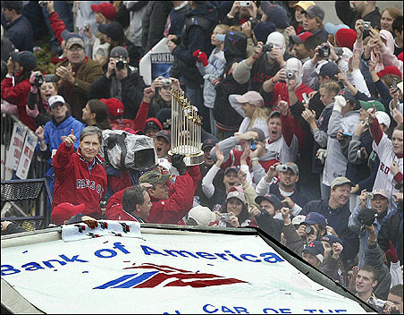 Red Sox CEO John Henry and pitcher Curt Schilling hold up the World Series trophy on Boylston Street.