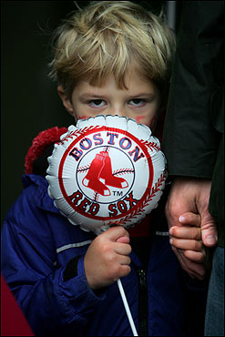 Rory Carney, 5, of Wellesley, shyly hides behind his Sox balloon. Maybe seeing the World Series champs will bring him out of his shell.