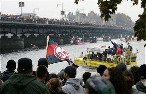 Red Sox fans line the banks of the Charles River and the Mass. Avenue Bridge to salute their team.
