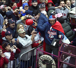 Aces Derek Lowe and Pedro Martinez greet excited fans along Boylston Street.
