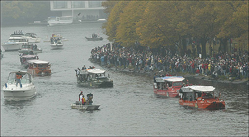 Duck boats go past the Boston side of the Charles River aproaching the Longfellow Bridge during the Sox parade.