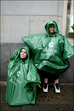 Brothers Jake, 12, (left) and James Callanan, 8, of Dedham, wait in the rain along Boylston Street.