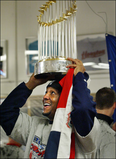 Pedro Martinez, with the Dominican flag and the World Series trophy, has his hands full as the celebration begins.