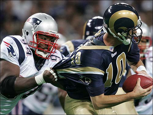 Ty Warren has a handful of Marc Bulger's jersey as he sacks the Rams quarterback during the first quarter.