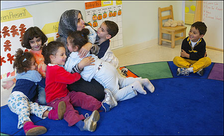 Head teacher Mervat Zaghloul got a group hug last month during an end-of-the-day song about hugging at circle time at Al Bustan school in Cambridge. Adam Maati is at right.