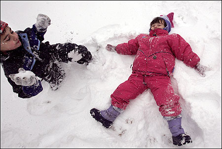Paige McCraven, 3, made a snow angel as her 5-year-old brother, Jack, hoisted a snowball in their Newbury backyard.