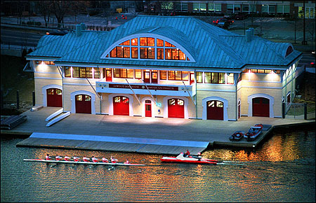 Boston University crew team members rowing past the DeWolfe Boathouse.