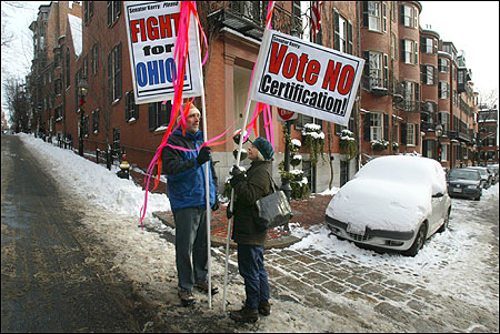 Ian Harrington and Heleni Thayre of the Coalition Against Election Fraud kept a vigil outside Senator John F. Kerry's home in Louisburg Square yesterday. The demonstrators want Kerry to oppose approval of the Electoral College results Jan. 6.