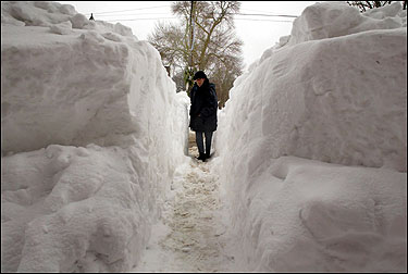 John Davis of Hyannis found some amusement in having to walk sideways to squeeze through a path between high mounds of snow to get from Main Street in downtown Hyannis to the sidewalk.