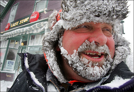A snow-coated Ted Suchecki used a snow blower to clear snow from the front of his store, The Last Stop, on East Main Street in Gloucester.