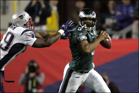 Donovan McNabb scrambles as he's pursued by Rosevelt Colvin (center) and Roman Phifer.