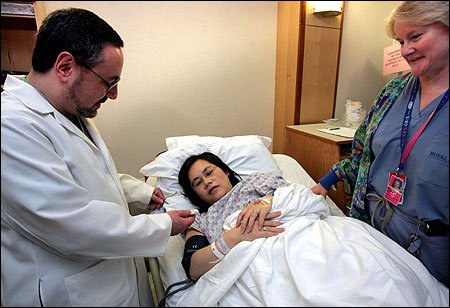 At Brigham and Women's Hospital, Dr. William Camann showed Teresa Wang how epidural drugs are administered.