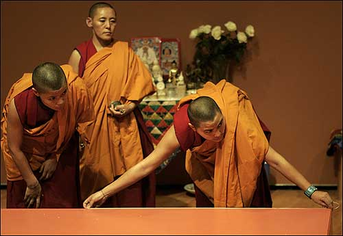 Kelsang Palmo (left) and Tenzin Lopsang (center) looked on as Palhdon continued measuring.