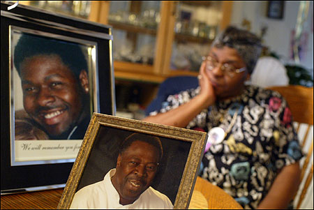 Emma Holman sat in the kitchen of her Roxbury home last month remembering her husband, Sam, (center) and her son Reggie.