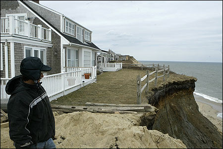 Arnoldo Tejada peered toward Nantucket's Siasconset Beach on Friday, standing near where erosion of a cliff has endangered an estimated 100 homes along Baxter Road.