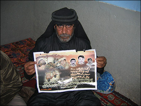 Abd Ali al-Alawi, whose nephews were beaten to death by Iraqi police, held up a poster that portrays them and a third victim as martyrs. A probe led to the arrest of six police officers