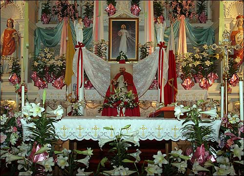 The altar at St. Stanislaus was decorated with a photograph of Pope John Paul II and flanked with flowers for him in the days leading up to his death.