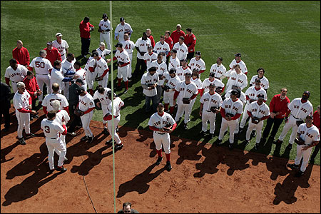Red Sox past and present watch as the 2004 championship banner is raised in center field during a pregame ceremony.