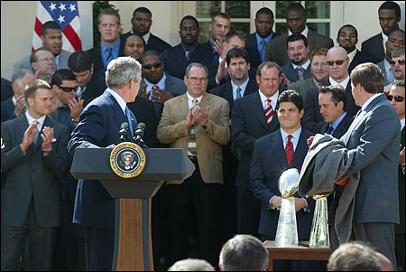 President Bush turned to praise Tedy Bruschi (lower right), the Patriots linebacker who suffered a stroke in February, for ''incredible courage on and off the field'' during ceremonies at the White House yesterday. The Super Bowl champions were making their second straight visit and their third in four years.