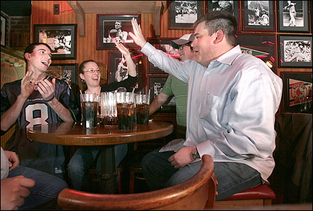 Jay Ceresia high-fived Heather DeSimone as they and teammates Richie Conlon (L) and Matt Calvey celebrated a right answer at Pizzeria Uno's trivia night in Cambridge.