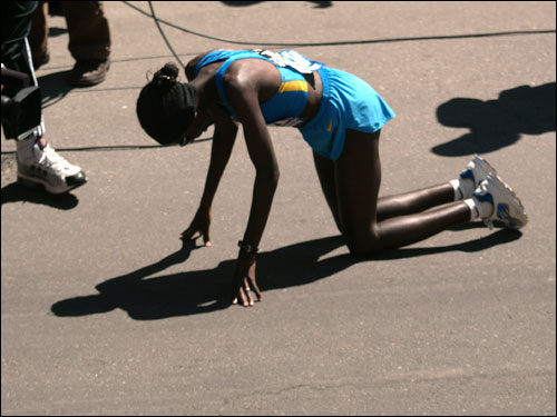 Kenyan's Catherine Ndereba owned the road, then bowed to the pavement after crossing the finish line.