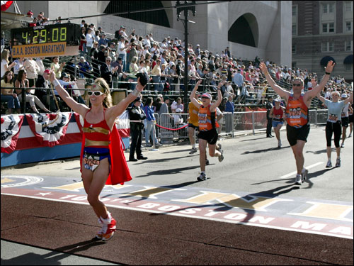 Gretchen Lammeman, 33, of Beaumont, Texas, dressed as Wonder Woman, throws her hands in the air as she crosses the finish line.