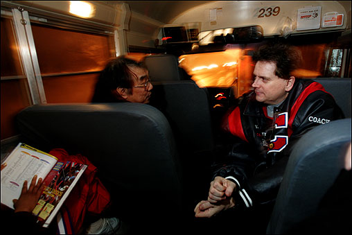 Charlestown headmaster and basketball booster Michael Fung rides on the team bus for all away games. He often critiques coach Jack O'Brien's performance, and the coach critiques the headmaster's right back. Here, they confer after Charlestown's tournament win over East Boston.