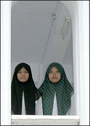 Lena Rachmawati (R) and Ninikrohmawati, both 15, are students at a moderate Indonesian school.