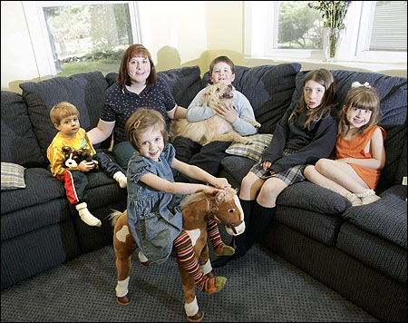 Kathryn Worthen with her five children, (clockwise from left) Colin, Christian — with family dog, Gabbie — Caitlin, Molly, and Madeleine. The Worthens are hoping DSS will revise its ''Rule of Six'' so they can adopt two siblings.